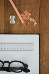 Book, pencil, spectacles, scale, pencil and sharpener on wooden tableの写真素材 [FYI02235696]