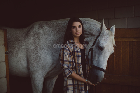 Portrait of woman standing with horseの写真素材 [FYI02235731]