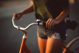 Mid section of woman riding bicycleの写真素材 [FYI02235733]