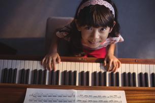 Overhead portrait of girl playing piano in classroomの写真素材 [FYI02235736]