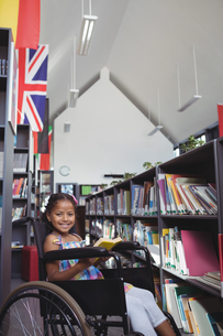 Smiling girl with book on wheelchair in libraryの写真素材 [FYI02235740]