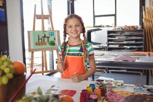 Portrait of happy girl holding paintbrushesの写真素材 [FYI02235770]