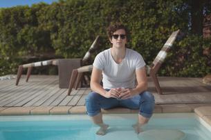 Handsome man sitting near pool sideの写真素材 [FYI02235772]