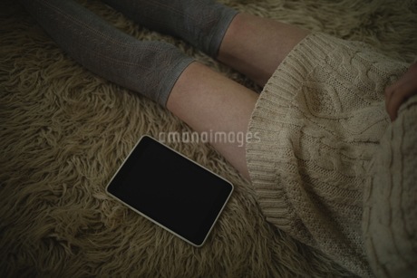 Woman sitting on the floor with digital tabletの写真素材 [FYI02235773]
