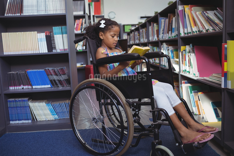 Girl reading book on wheelchair in libraryの写真素材 [FYI02235792]