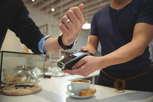 Customer paying with NFC technology on smart watch in coffee shopの写真素材 [FYI02235794]