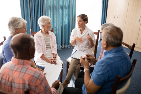 High angle view of female doctor talking to seniors while sitting on chairsの写真素材 [FYI02235812]