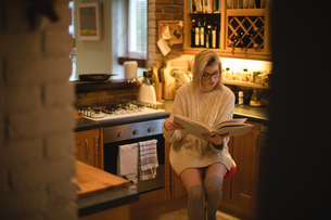 Woman reading a book in kitchenの写真素材 [FYI02235815]