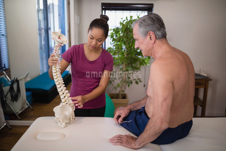 Female therapist explaining shirtless senior male patient with artificial spineの写真素材 [FYI02235882]