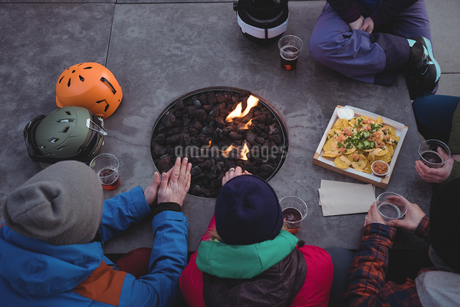 Group of skiers rubbing their hands near fireplaceの写真素材 [FYI02235901]
