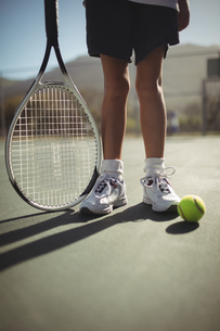 Girl with tennis racket and ball on courtの写真素材 [FYI02235929]