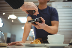 Customer making contactless payment in coffee shopの写真素材 [FYI02235945]