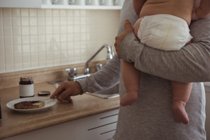 Mid section of father preparing breakfast while holding his babyの写真素材 [FYI02235946]