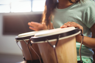 Mid section of girl playing bongo drums in classroomの写真素材 [FYI02235981]