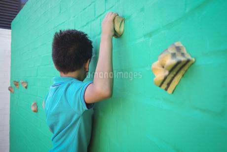Side view of boy climbing wallの写真素材 [FYI02236012]