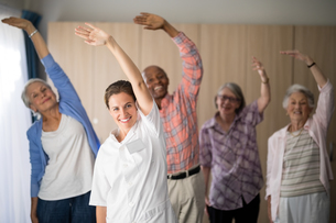 Portrait of smiling female doctor and seniors exercising with arms raisedの写真素材 [FYI02236022]