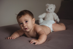 Cute baby lying on tummy in bedroomの写真素材 [FYI02236027]