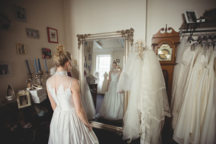 Young bride in a white dress looking into mirrorの写真素材 [FYI02236050]