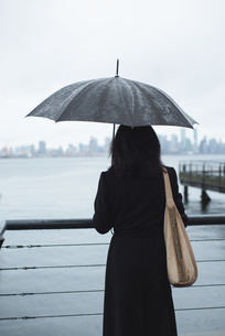 Woman holding umbrella while standing by river during rainy seasonの写真素材 [FYI02236051]