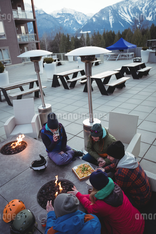 Group of skiers rubbing their hands near fireplaceの写真素材 [FYI02236055]