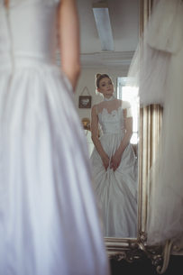 Young bride in a white dress looking into mirrorの写真素材 [FYI02236058]