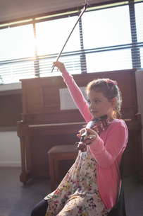 Cute girl rehearsing violin in music classの写真素材 [FYI02236059]