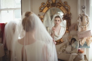 Young bride in a white dress looking into mirrorの写真素材 [FYI02236070]