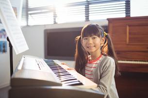 Portrait of smiling girl practicing pianoの写真素材 [FYI02236091]