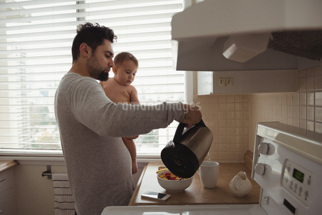 Father preparing breakfast while holding his babyの写真素材 [FYI02236097]