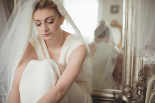 Thoughtful young bride in a white dress relaxingの写真素材 [FYI02236122]