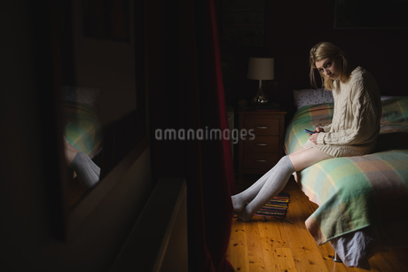 Woman sitting and using mobile phone on bedの写真素材 [FYI02236127]