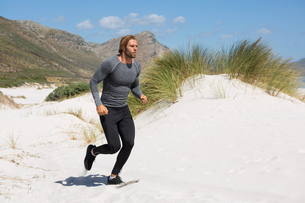 Male athlete running at beach by mountainの写真素材 [FYI02236141]