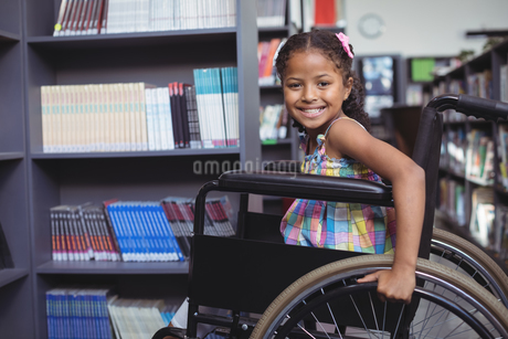 Smiling girl on wheelchair at libraryの写真素材 [FYI02236160]