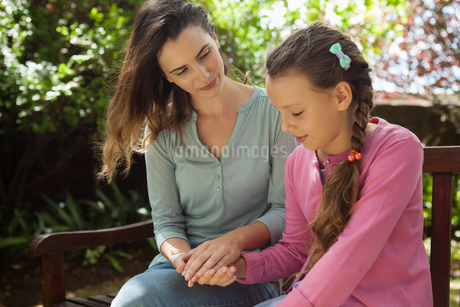 Mother looking at girl while holding hands on wooden benchの写真素材 [FYI02236161]