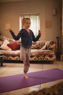 Girl performing yoga in living roomの写真素材 [FYI02236173]