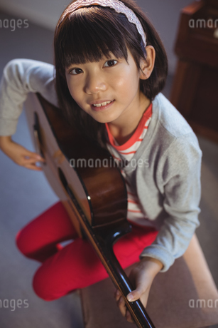 High angle portrait of girl practicing guitarの写真素材 [FYI02236190]