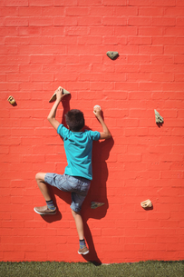 Boy climbing orange wallの写真素材 [FYI02236191]