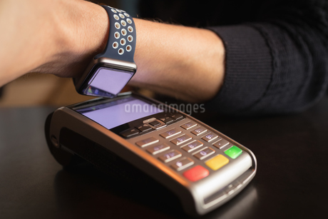 Close-up of man paying through smartwatch using NFC technologyの写真素材 [FYI02236201]