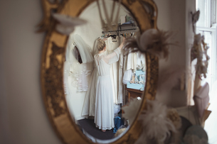 Reflection of bride selecting wedding dress from clothes hanger in the mirrorの写真素材 [FYI02236208]