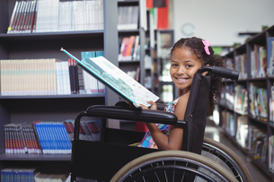 Smiling girl with book on wheelchairの写真素材 [FYI02236222]
