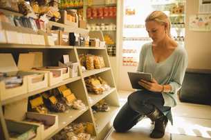 Saleswoman using digital tablet by products on shelvesの写真素材 [FYI02236226]