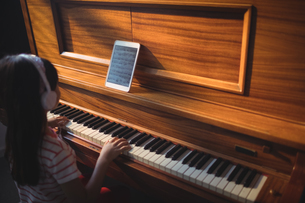 High angle view of girl wearing headphones while practicing piano in classroomの写真素材 [FYI02236236]
