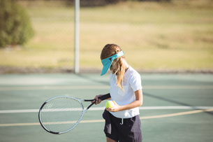 Girl holding tennis ball and racket on courtの写真素材 [FYI02236241]