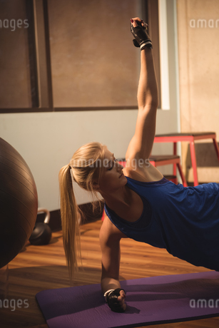 Fit woman performing fitness exercise on a exercise matの写真素材 [FYI02236261]