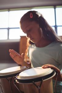Girl practicing bongo drums in classroomの写真素材 [FYI02236265]