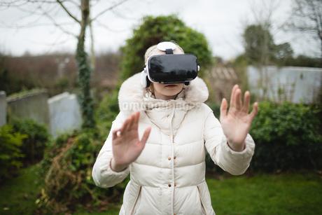 Woman in fury coat using virtual reality headsetの写真素材 [FYI02236273]