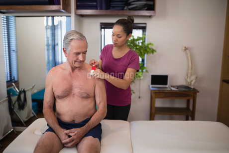 Female therapist applying elastic therapeutic tape on shoulder of shirtless senior male patientの写真素材 [FYI02236310]