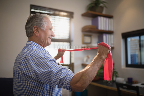 Side view of senior man pulling resistance band in hospital wardの写真素材 [FYI02236315]