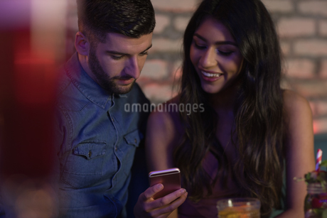 Couple using mobile phone in barの写真素材 [FYI02236427]