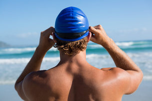 Rear view of shirtless athlete standing by seaの写真素材 [FYI02236455]